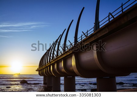 Umhlanga Pier in Durban South Africa in the Morning Sunrise over the Horizon of the Indian Ocean - stock photo