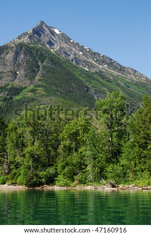 ummer view of upper waterton lake and mountains in goat haunt ranger station, glacier national park, montana, usa - stock photo