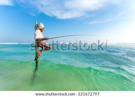 UNAWATUNA, SRI LANKA - MARCH 9, 2014: Elderly stilt fisherman at Hikkaduwa Beach. Most real stilt fishermen have been long gone. Today it's mainly young boys posing as stilt fishermen for tourists. - stock photo