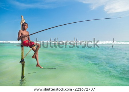 UNAWATUNA, SRI LANKA - MARCH 9, 2014: Young stilt fisherman at Hikkaduwa Beach. Most real stilt fishermen have been long gone. Today it's mainly young boys posing as stilt fishermen for tourists. - stock photo