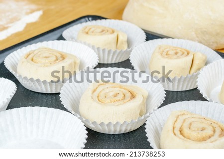 Unbaked buns in disposable white paper cups on metal plate. - stock photo