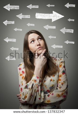 Uncertain girl is looking at arrows. Girl full of doubts and hesitation. - stock photo