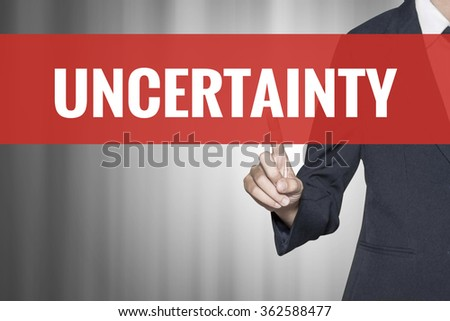 Uncertainty word on virtual screen push by business woman red tab - stock photo