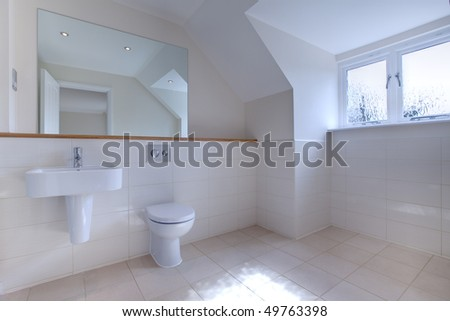 Uncluttered modern chic bathroom with large mirror, tiled walls, wall mounted sink and toilet. - stock photo