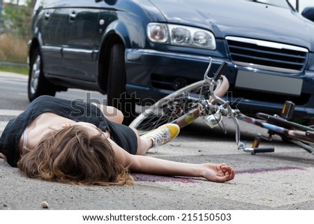 Unconscious female cyclist lying on street after road accident - stock photo