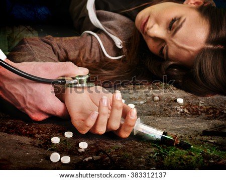 Unconscious woman addicted keeps syringe and lying on  dirty floor. Death from drugs concept. - stock photo