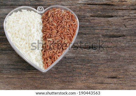 Uncooked basmati rice and brown rice in a plastic bowl on wooded background - stock photo