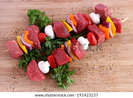 Uncooked beef kebabs with vegetables and spices on wooden board - stock photo