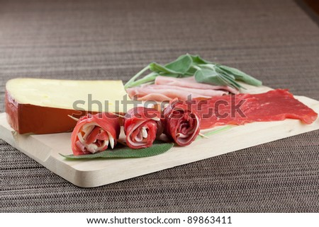 uncooked beef rolls with ham and cheese with raw ingredients over a wood board - stock photo