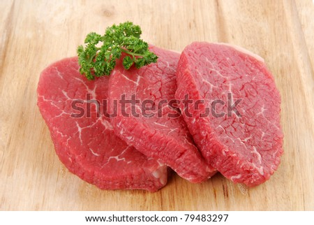 Uncooked beef steaks on a cutting board with garnish - stock photo