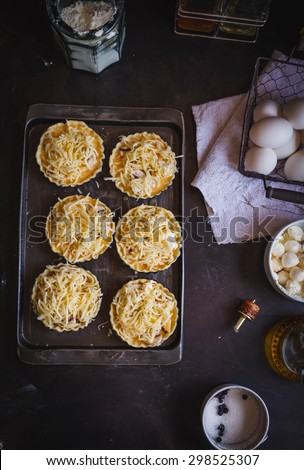 Uncooked cheese and mushroom mini tart over on a oven sheet with various ingredients from above on dark metallic background. Rustic dark atmosphere. See series. Step on step. - stock photo