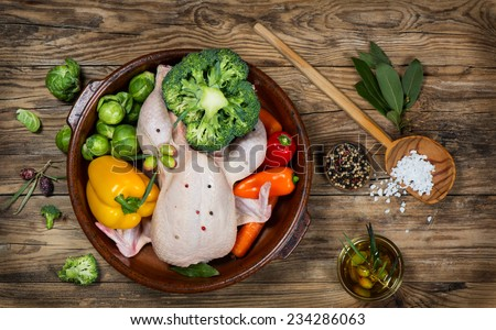 uncooked chicken with vegetables in a pan on a old rustic wooden table, top view - stock photo