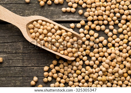 uncooked chickpeas in wooden scoop - stock photo