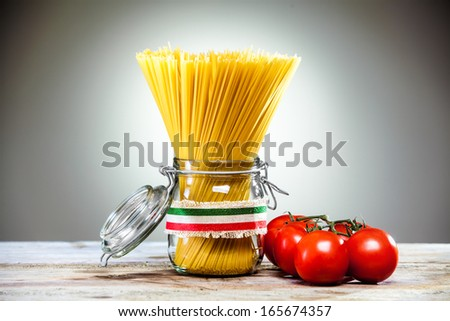 Uncooked dried Italian spaghetti tied with a ribbon in the colours of the national flag - red, white and green - standing in a glass jar with fresh ripe red tomatoes alongside - stock photo