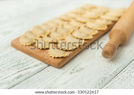 Uncooked dumplings on the wooden desk. - stock photo