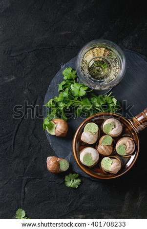 Uncooked Escargots de Bourgogne - Snails with herbs butter, gourmet dish, in traditional ceramic pan with parsley and glass of white wine on stone slate over black textured background. Top view. - stock photo