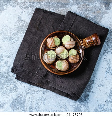 Uncooked Escargots de Bourgogne - Snails with herbs butter, gourmet dish, in traditional ceramic pan over blue textured background. Top view. Square image - stock photo