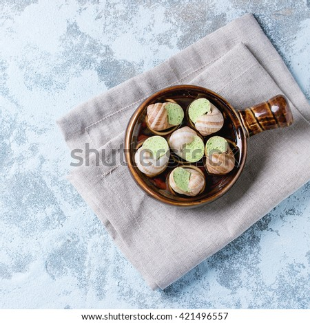 Uncooked Escargots de Bourgogne - Snails with herbs butter, gourmet dish, in traditional ceramic pan over blue textured background. Top view. With copy space. Square image - stock photo