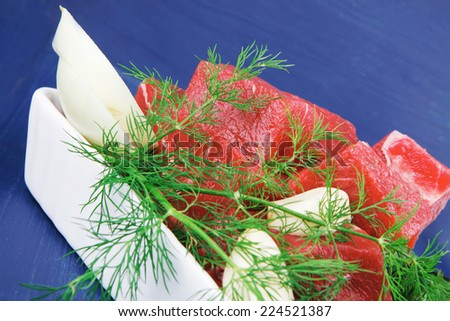uncooked fresh beef meat chunks on white bowls with green hot peppers and vegetables serving over blue wooden table - stock photo