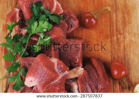 uncooked fresh beef meat chunks on wooden cutting plate with green hot and red peppers isolated over white background - stock photo