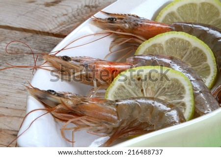 uncooked fresh raw shrimp on a white plate on a wooden base garnished with fresh slices of yellow lemon - stock photo
