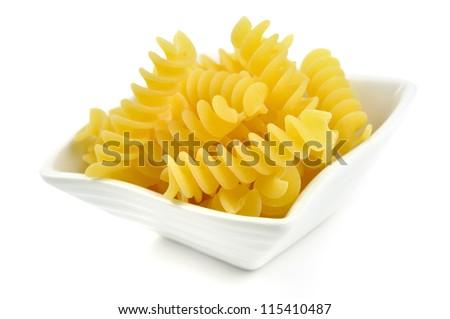 Uncooked fusilli in a small bowl, italian pasta, white background - stock photo
