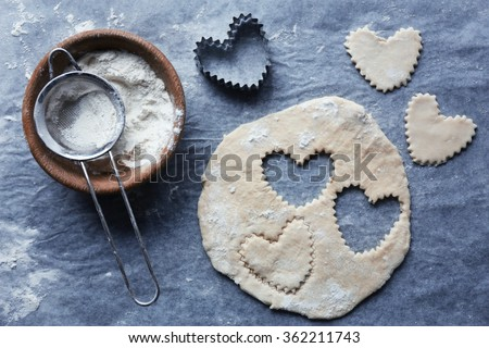 Uncooked heart shaped biscuits on a table - stock photo
