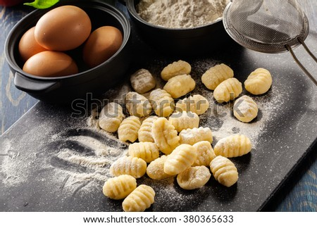 Uncooked homemade gnocchi on black cutting board - stock photo