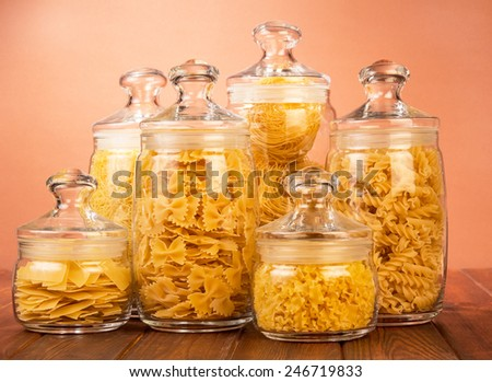 Uncooked italian pasta in glass bottles on wooden table - stock photo