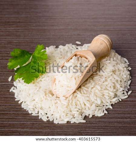 Uncooked jasmin rice in a wooden spoon - stock photo