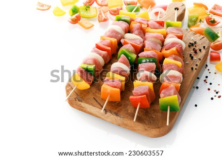 Uncooked meat and vegetable kebabs with colorful red, yellow and green sweet bell pepper, onion and tomato ready on a wooden board for grilling with fresh ingredients behind - stock photo