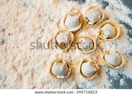 Uncooked meat dumplings lies on right side of the table - stock photo