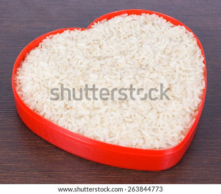 Uncooked parboiled rice in a red heart plate  - stock photo