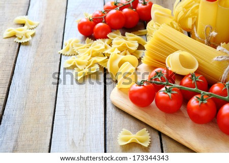 uncooked pasta and cherry tomatoes branch, food closeup - stock photo