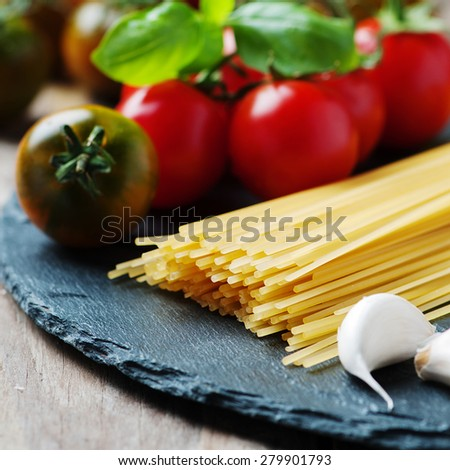 Uncooked pasta with tomato, basil and oil, selective focus and square image - stock photo