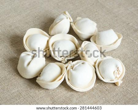 Uncooked pelmeni on a gray sackcloth - stock photo