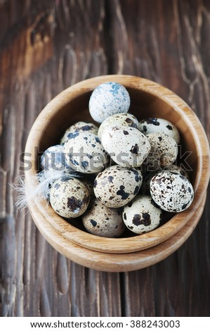 Uncooked quail eggs in the wooden bowl, selective focus - stock photo