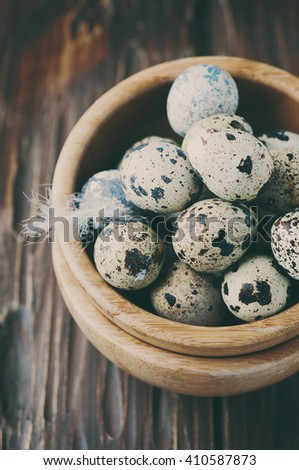 Uncooked quail eggs in the wooden bowl, selective focus and toned image - stock photo