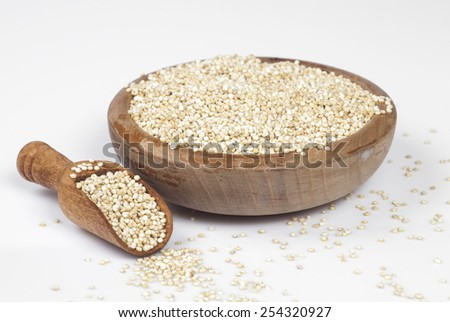Uncooked quinoa in the wooden bowl and spoon. Selective focus. - stock photo