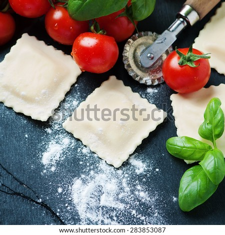 Uncooked ravioli with tomato and basil, selective focus and square image - stock photo