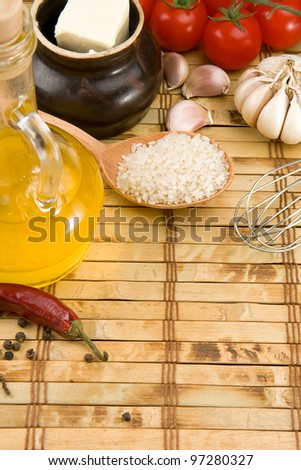 uncooked raw rice and vegetable on wood background - stock photo