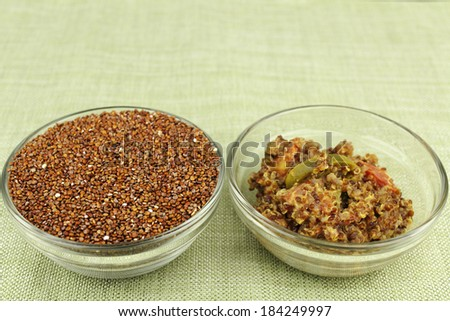 Uncooked red quinoa seeds in a round clear glass dish next to a tasty and healthy appetizer bowl of cooked quinoa mixed with jalapeno slices, tomatoes and parmesan cheese on a green place mat. - stock photo