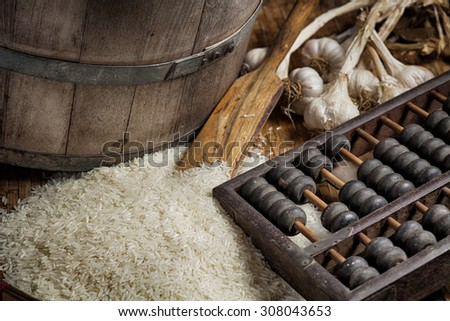 Uncooked rice, garlic,  on a wooden tray , still life - stock photo