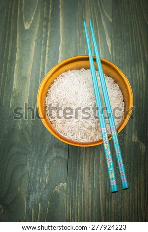 Uncooked rice grains in wood bowl - stock photo