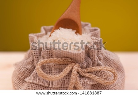 Uncooked rice in a sack over dark yellow background close-up - stock photo