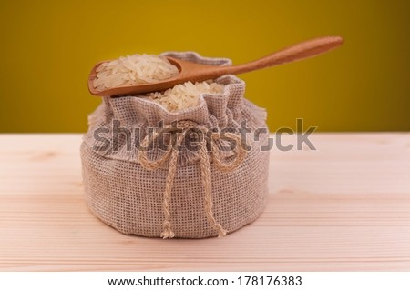 Uncooked rice in bamboo spoon on a burlap bag over dirty yellow background - stock photo