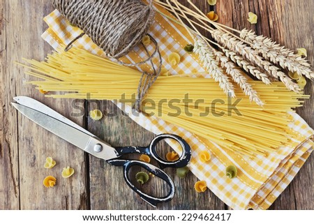 uncooked spaghetti on a yellow towel, old pair of scissors and a skein of linen thread on a wooden background. italian food ingredients - stock photo