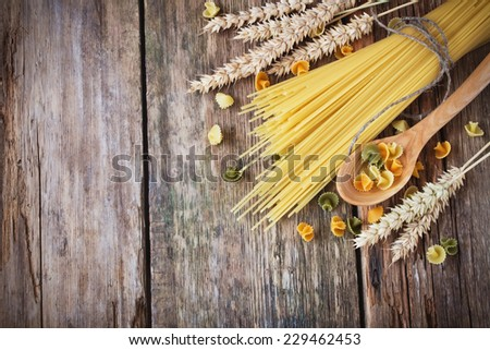 uncooked spaghetti, wheat ears and a wooden spoon on a wooden background. italian food ingredients. copy space background - stock photo