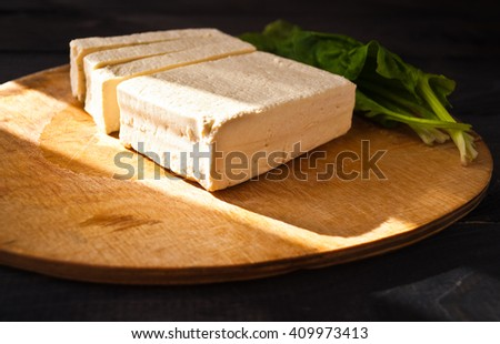 Uncooked tofu slices and green leaves of fresh spinach on cutting board and sunlight from the window - stock photo