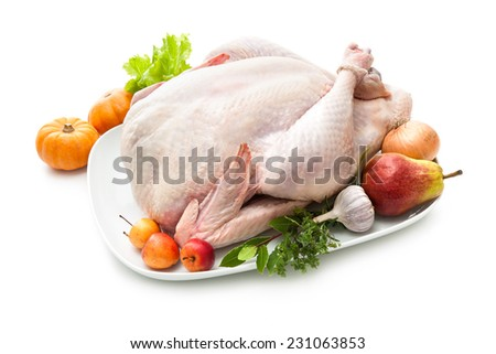 Uncooked turkey with herbs isolated on white background - stock photo